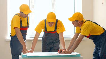 Bauherren, die mit Dokumenten auf der Baustelle arbeiten. Gebäude- und Hausrenovierung.