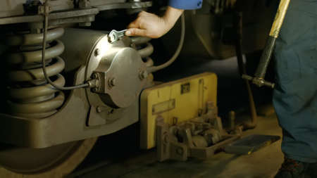 Mechanic repairing train at the depot. Wheel of subway train close up. Technical specialist tightening the screws.