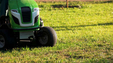 Green lawn mower tractor. Lawn mower tractor outdoors on a sunny day, cropped image. Фото со стока