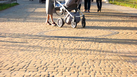 Woman with a stroller walking in the park. Cobblestones surface. People walking outdoor on a sunny day. 写真素材 - 124675931