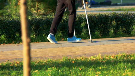 Young man walking with crutches in park. Male person with injured leg outdoors, cropped image. Stock Photo
