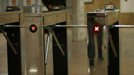 Turnstiles in the subway. People pass through the turnstiles. Check point. 版權商用圖片
