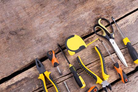Bauwerkzeuge auf hölzernem Hintergrund. Set mit verschiedenen Instrumenten zur Reparatur an alten Brettern. Platz für Text.