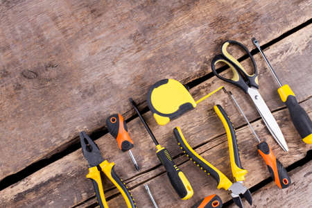 Construction tools on wooden background. Set of different instruments for repair on old boards. Space for text.