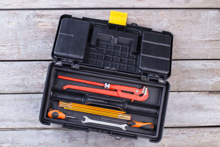 Construction tools in box, top view. Different tools in tool case on wooden background. Construction and repair concept.