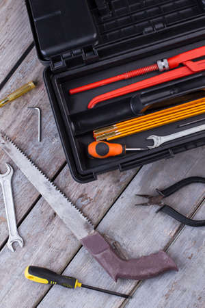 Tool box on wooden background. Box set of metal working tools on wooden boards.