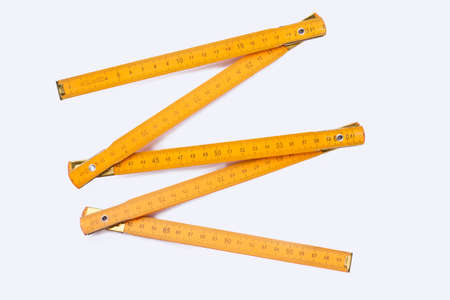 Yellow wooden ruler isolated on white background. Wooden centimeter ruler. Carpenters tool.