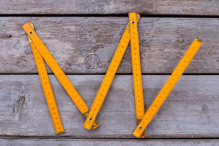 Yellow wooden meter on wooden background. Tool for carpenter.