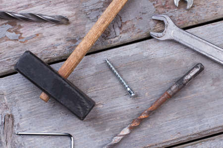 Construction tools on wooden background. Hammer, spanner, screws and drill bits on old wooden boards.