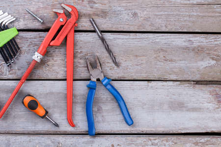 Different construction tools on the wooden background. Adjustable wrench, screwdriver, pliers and Allen keys. Space for text.