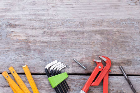 Various tools for construction on wooden background. Folding ruler, set of Allen keys, adjustable wrench and drill bit. Space for text. Stock Photo