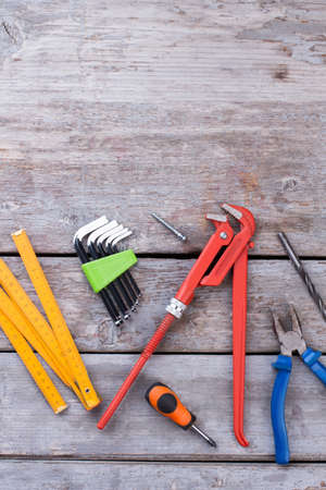 Construction tools on wood background. Cracked wooden surface with different tools and instruments for repair. Top view with copy space.