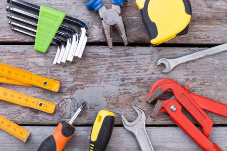 Set of construction tools on wooden background. Various tools for repair on wooden surface with copy space. House renovation concept.