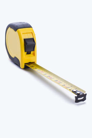 Construction measuring tape on white background. Retractable measuring tape, vertical image. Stock Photo