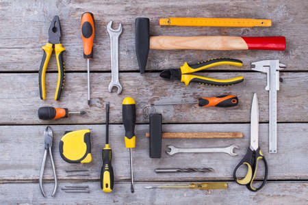 Construction tools on wooden background. Flat lay various building tools on rustic boards background. Repair concept.