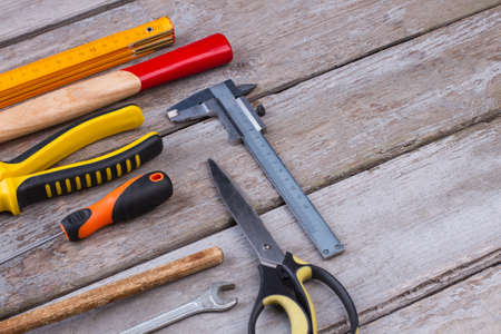 DIY construction tools on wooden background. Working tools on a wooden boards: screwdriver, pliers, hammer, ruler, scissors, wrench. Stock Photo