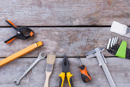 Flat lay carpenter tools on wooden background. Various construction instruments on wooden boards with copy space.