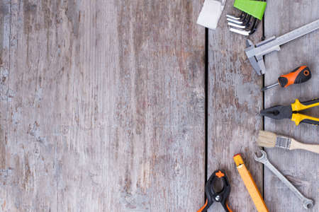 Tools kit on a wood background. Set of construction tools on wooden boards. Space for text.