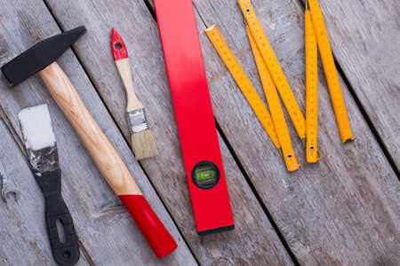 Repair tool kit background. Construction tools including palette-knife, hammer, paintbrush, spirit level and folding ruler on wooden background. Stock Photo