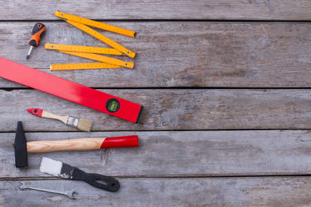 Working tools on wooden background. Tool kit including spatula, hammer, paintbrush, spirit level, folding ruler and screwdriver. Space for text.