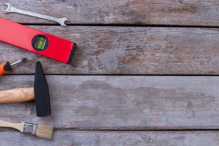 Different working tools on rustic wooden boards. Paintbrush, hammer, screwdriver, spirit level and spanner. Space for text.