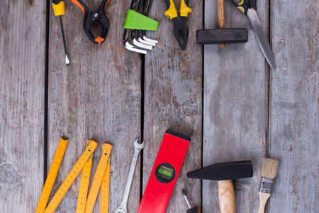 Different construction tools on wooden background. Assorted tools for repair on rustic wooden boards with copy space. Home renovation concept. Stock Photo