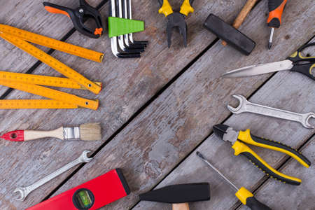 Border frame of construction tools on rustic background. Flat lay of various technician tools on old wooden boards. Stock Photo