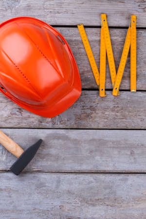 Hammer, hardhat and folding ruler. Construction tools on wooden background. Space for text.