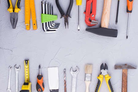 Background of construction tools with text space. Mechanic and carpenter tools on gray background with copy space.