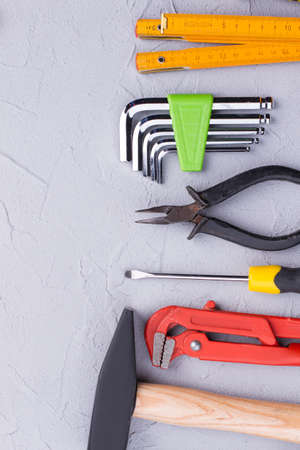 Set of construction tools. Hammer, adjustable wrench, screwdriver, cutting pliers, allen wrench key set and folding ruler. Space for text.