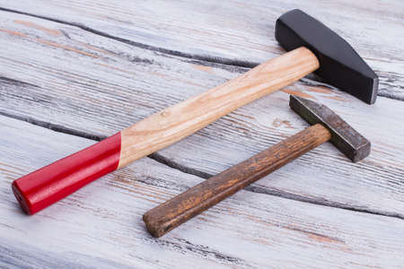 Old and new hammers on wooden background. Hammers with wooden handles on wood surface. Stock Photo