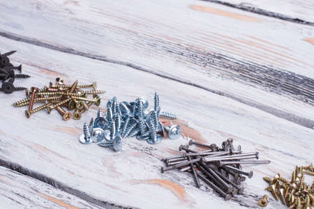 Screws nad nails on wooden background. Tools for wood work and repair. Space for text.