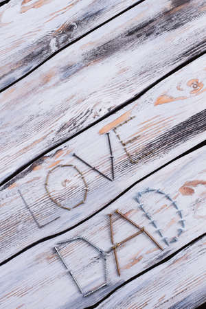 Love DAD text for Fathers Day. Inscription LOVE DAD made from metal screws and nails on wooden background, top view.