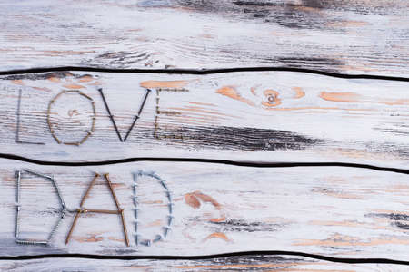 Greeting for Fathers Day made from metal screws. Inscription LOVE DAD on wooden background. Space for text.