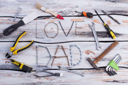 LOVE DAD background. Composition from different construction tools on wooden background. Fathers Day concept.