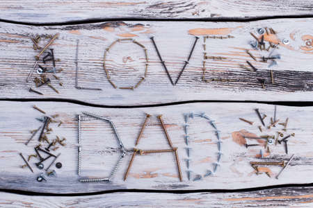 LOVE DAD inscription on wooden surface. Greeting card made of tools. Happy Fathers Day.
