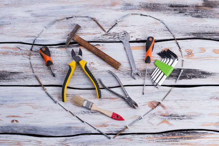Various construction tools on wooden background. Heart shape made from screws and different building tools. Composition for Fathers Day.