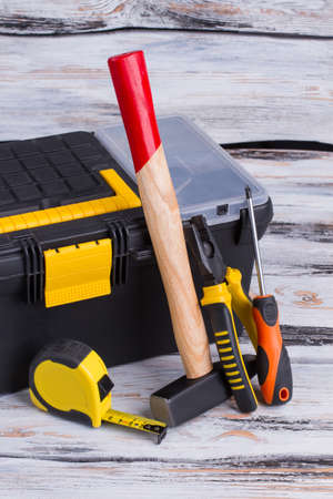 Tool kit on wooden background. Tool box, hammer, measuring tape, pliers and scewdriver. Repair concept.