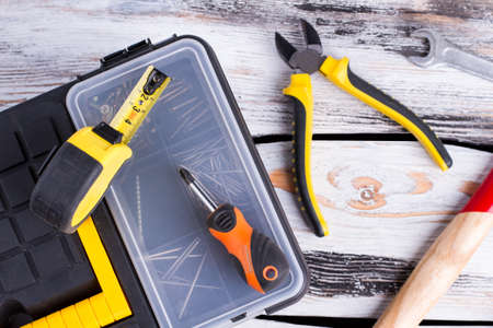 Tool box, pliers, screwdriver, hammer and ruler. Kit of construction tools and instruments on wood texture background.