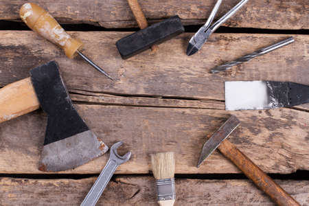 Frame from hand working tools on wooden floor. Old rusty tools and instrument for manual work and construction on wooden boards background.
