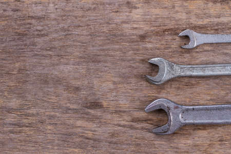 Spanners of different sizes, copy space. Wrenches on wooden background. Space for text.