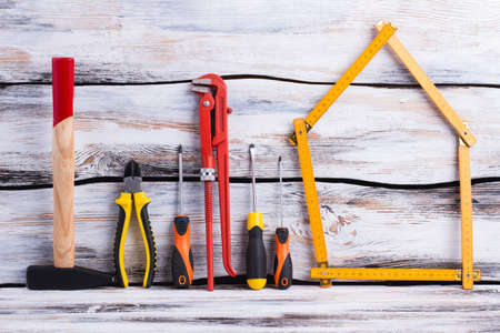 Construction tools on wooden background. Folding ruler in a shape of house, screwdrivers, hammer, adjustable wrench and pliers.