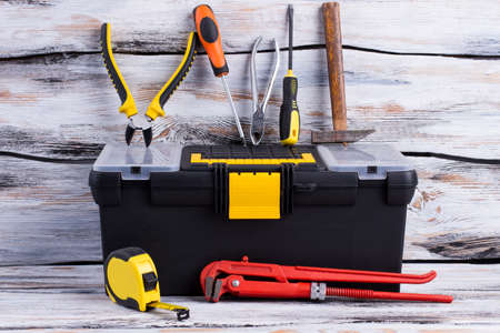 Tool box and various tools on wooden background. Adjustable wrench, tape measure, screwdriver, pliers, hammer and tool box. Stock Photo