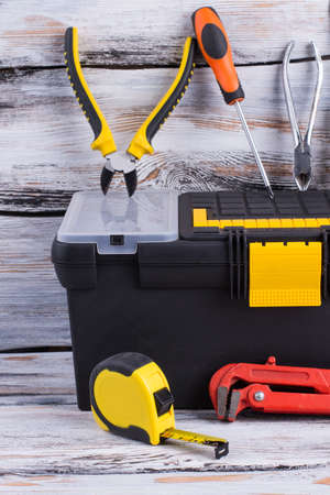 Tool box with different tools on wooden background. Tape measure, adjustable wrench, pliers, screwdriver and case with instruments. Carpenter tools background.