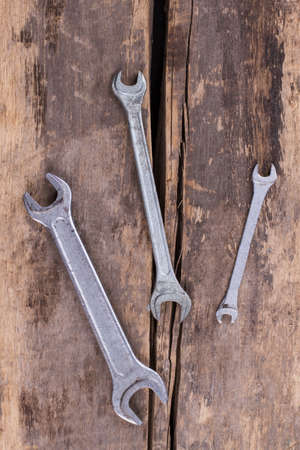 Wrenches on old wooden boards background. Tools on rustic planks, top view.