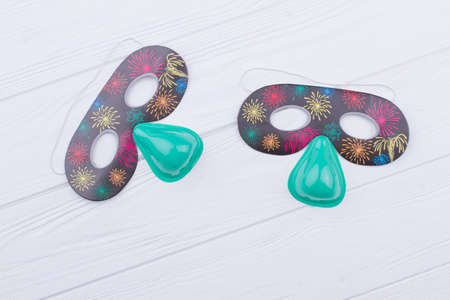 Kids eye mask for Birthday party. Accessories for New Year Eve party or costume party. White wooden background. Фото со стока