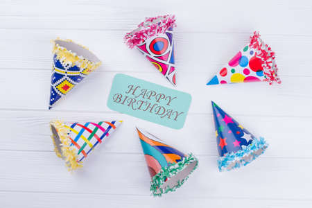 Happy Birthday card and party hats. Birthday composition with colorful party caps on white wooden background.