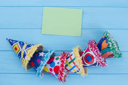 Cappelli da festa e carta di carta bianca. Gruppo di tappi colorati a cono per feste su tavole di legno di colore con spazio di testo. Priorità bassa dell'invito di festa.