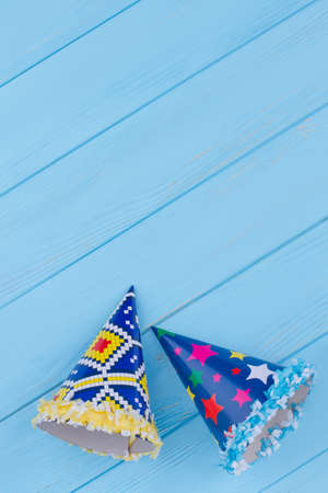 Party caps for Birthday celebration. Funny carton party hats on blue wooden background. Top view with copy space. Banco de Imagens