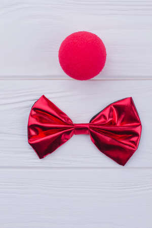 Red clown nose sponge and bow-tie. Flat lay composition with party items on white wooden background.